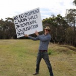 "Man holding banner at the Spring Gully public rally. ""No development in the Spring Gully environmental conservation zone""."